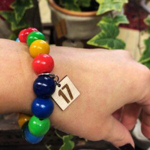 Armband med färgglada kulor och en tag som det står 17 på.