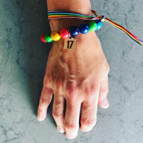 En hand sedd uppifrån med två färgglada armband.